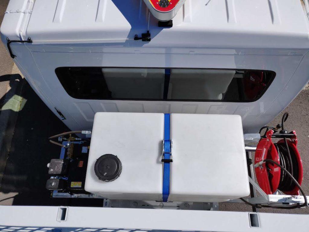 Vue du système de lavage haute pression logé entre la cabine et le plateau du camion.